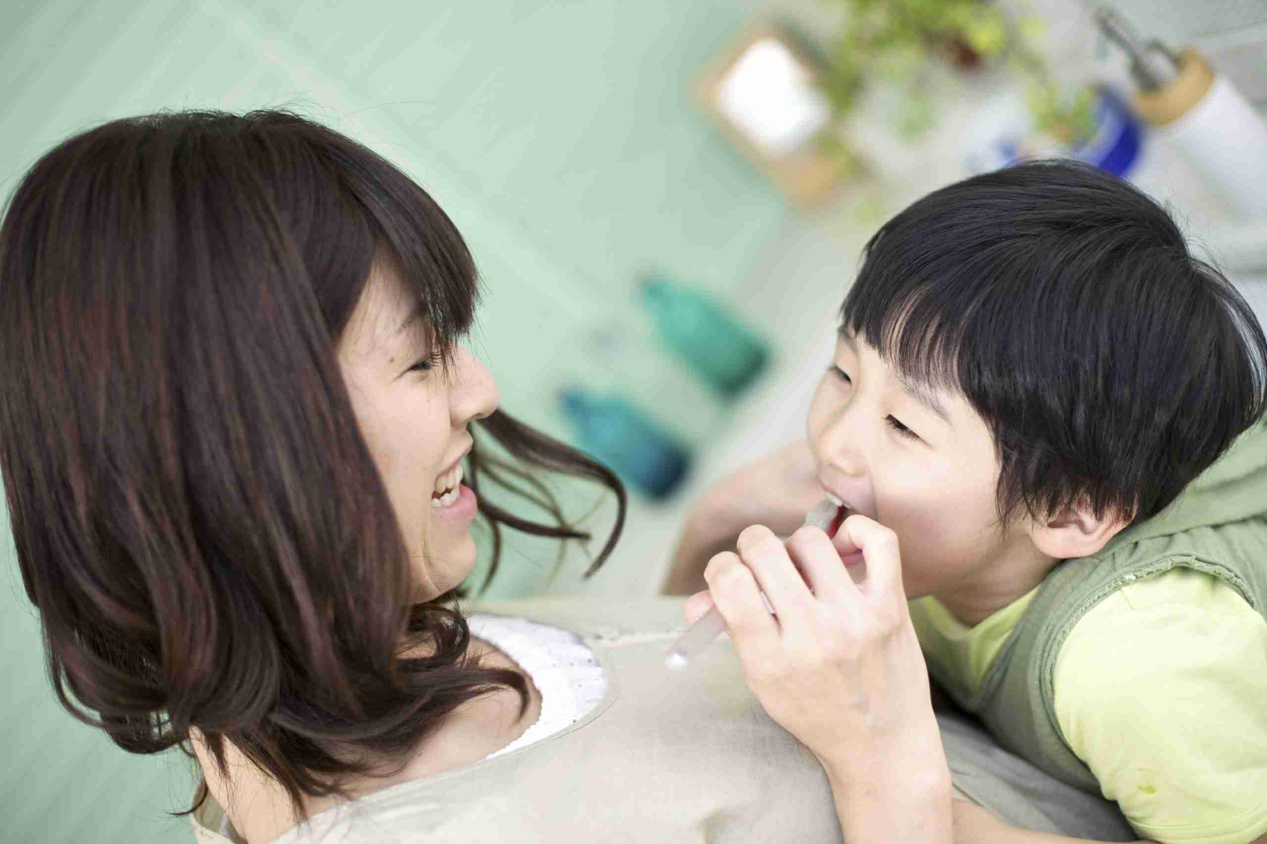 mother playing dentist with child